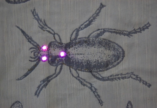 A bug painted on fabric with three little LED lights. (c) 2017 by Eloise O'Hare.