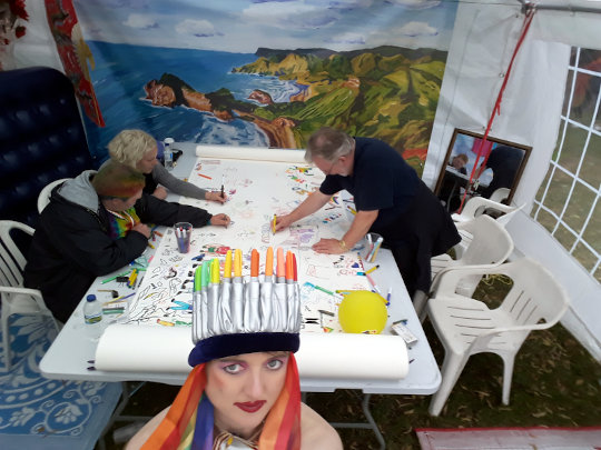 A photo of people drawing on a large roll of paper in the Dandies tent. (c) 2019 by Eloise O'Hare.