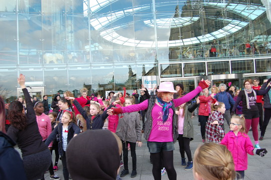People performing the 'Break the Chain' dance outside The Forum.